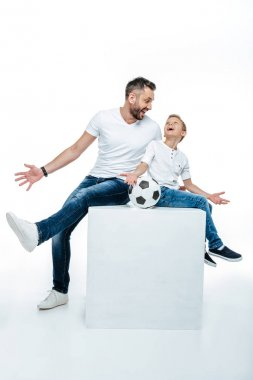 Father and son sitting with soccer ball