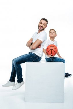 Father and son sitting with basketball ball