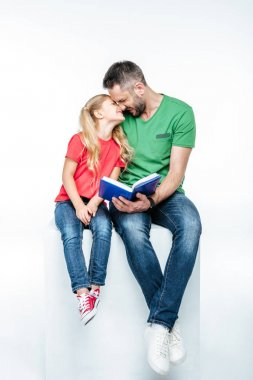 father and daughter sitting with book