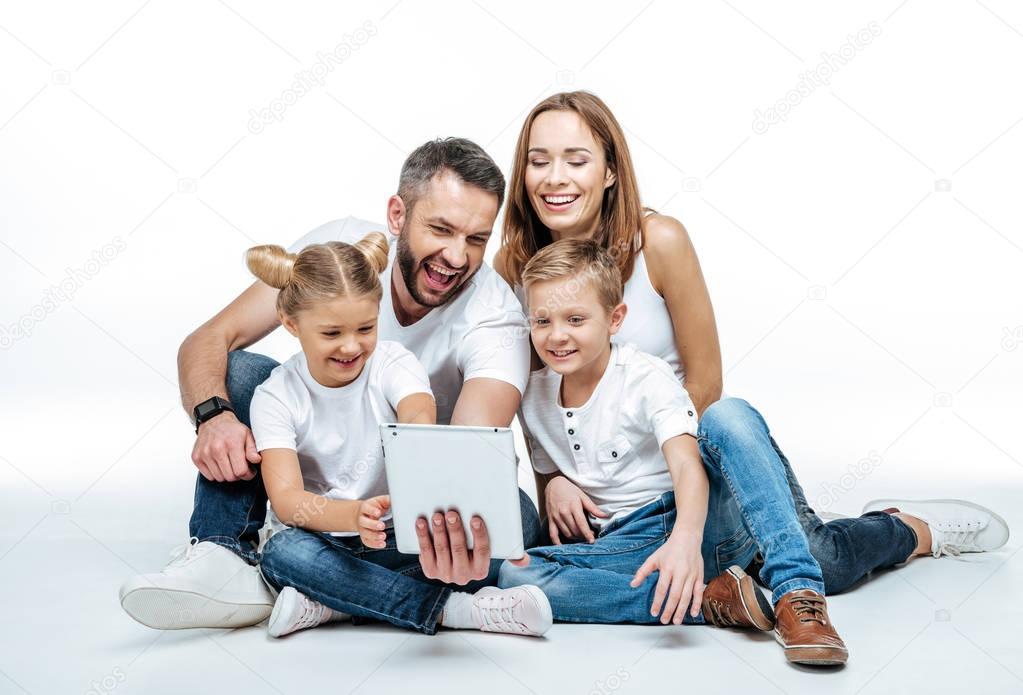 Smiling family using digital tablet