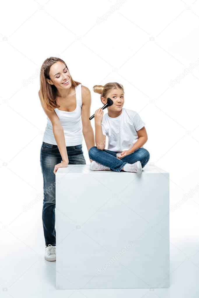 Mother looking at daughter with makeup brush
