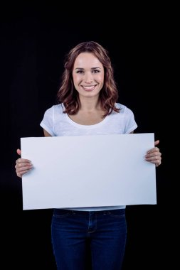 Smiling woman holding blank white card and looking at camera isolated on black stock vector