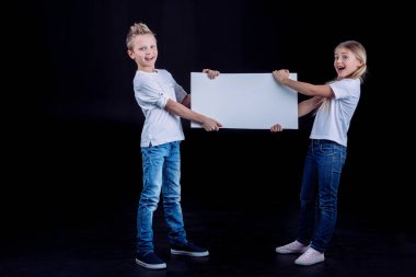 Smiling siblings with blank card