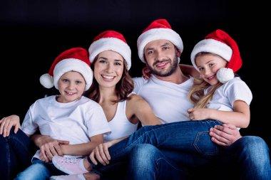 family in Santa hats looking at camera
