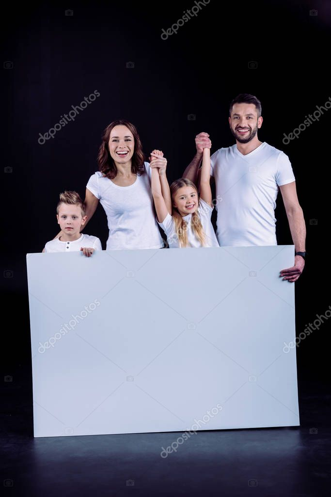 Family standing with blank white card