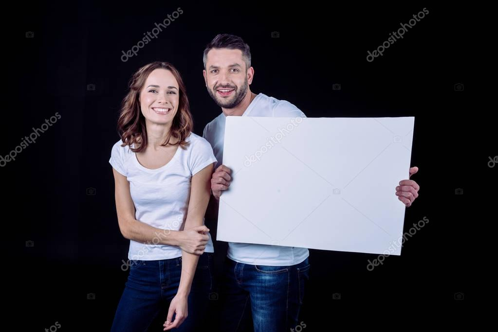 Smiling couple holding blank card
