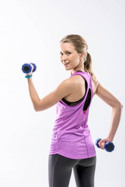 Blonde woman exercising with dumbbells and smiling at camera isolated on white stock vector