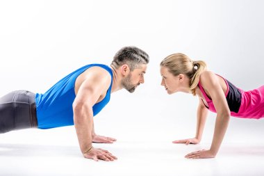 Sporty couple doing push ups and looking at each other stock vector