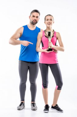 Sportive couple with award cup