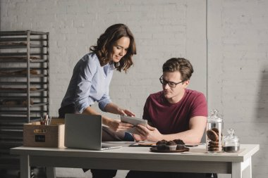 Man and woman using digital tablet