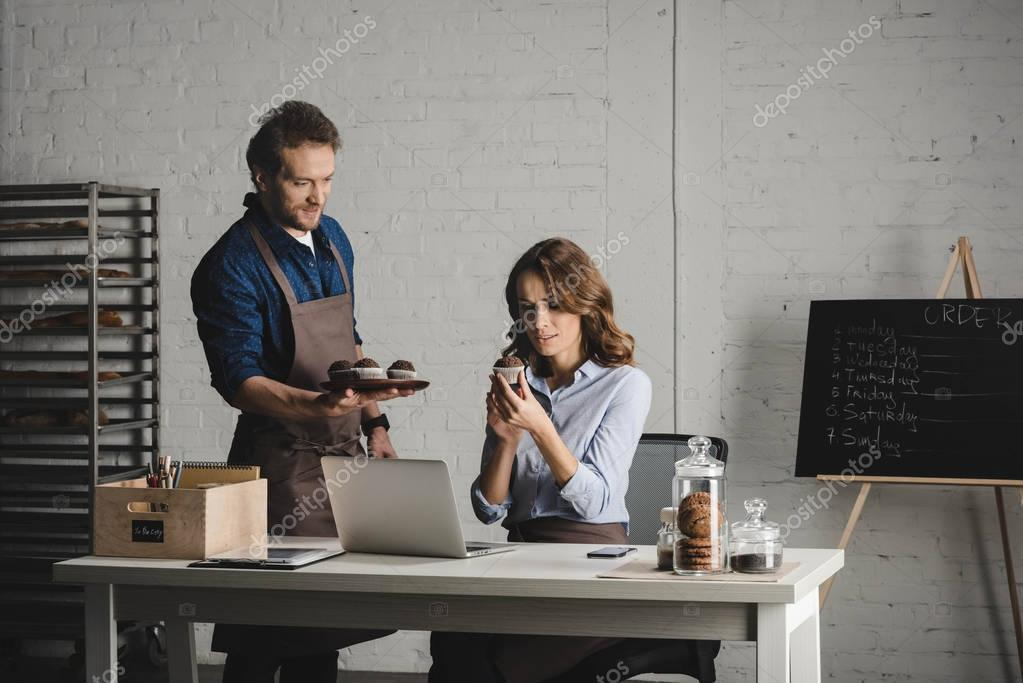 Man showing pastries to young woman