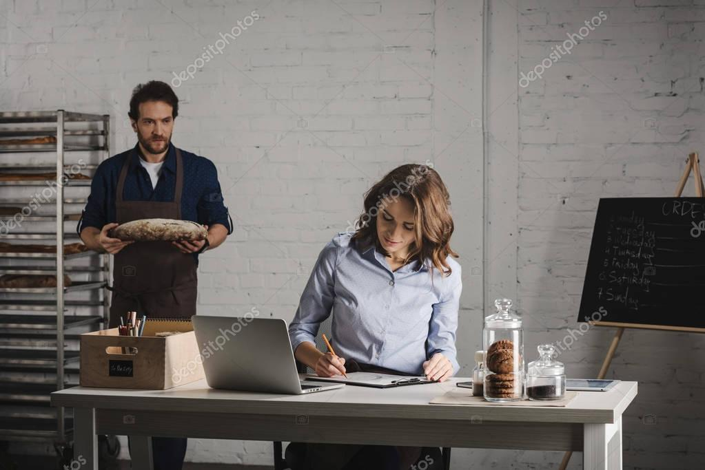 Woman making notes in bakehouse