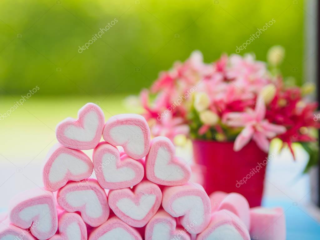 Closeup of sweet marshmallow in the shape of heart on wooden plate and flower at background.
