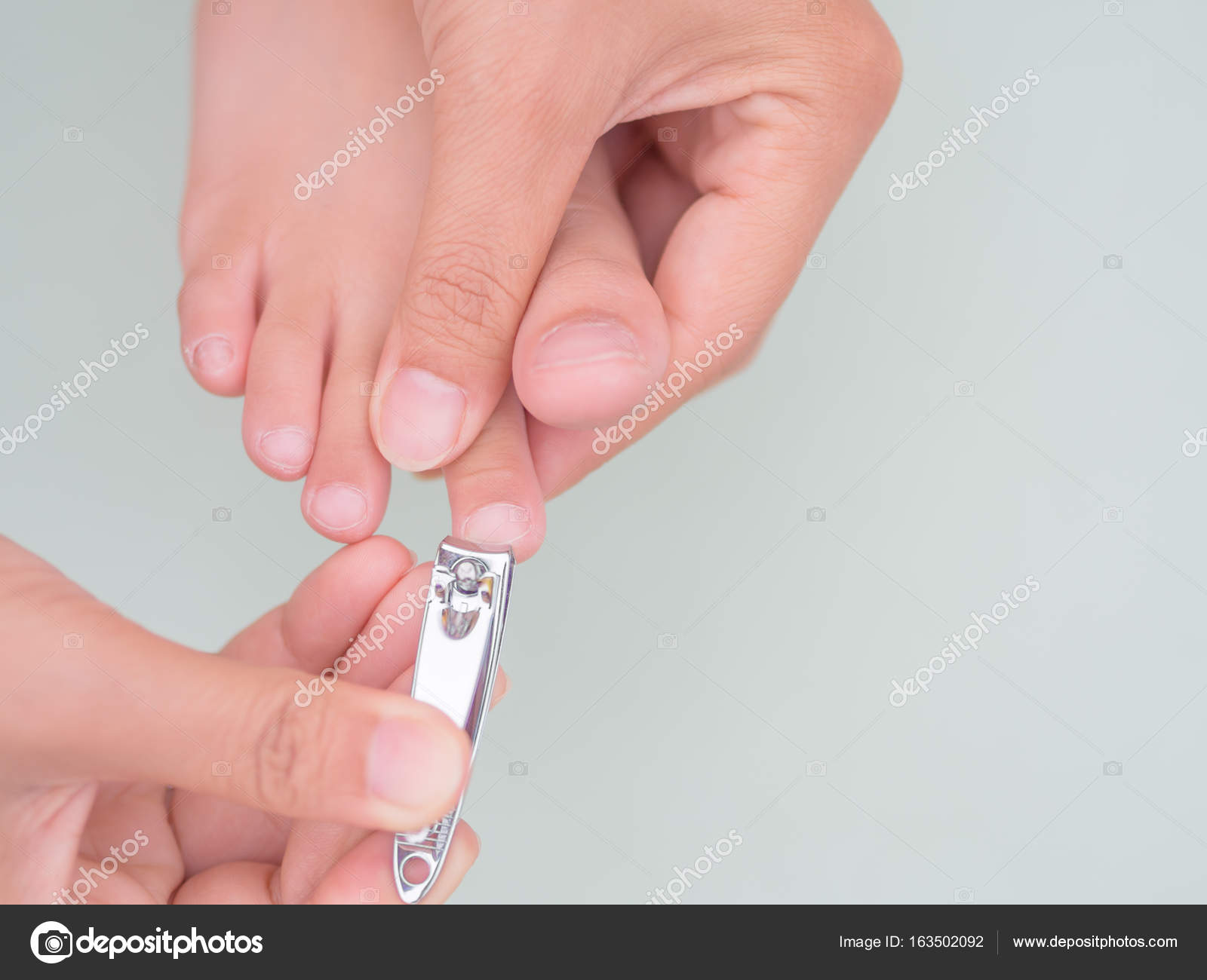 mother hand cut nails for kid — Stock Photo © spukkato #163502092