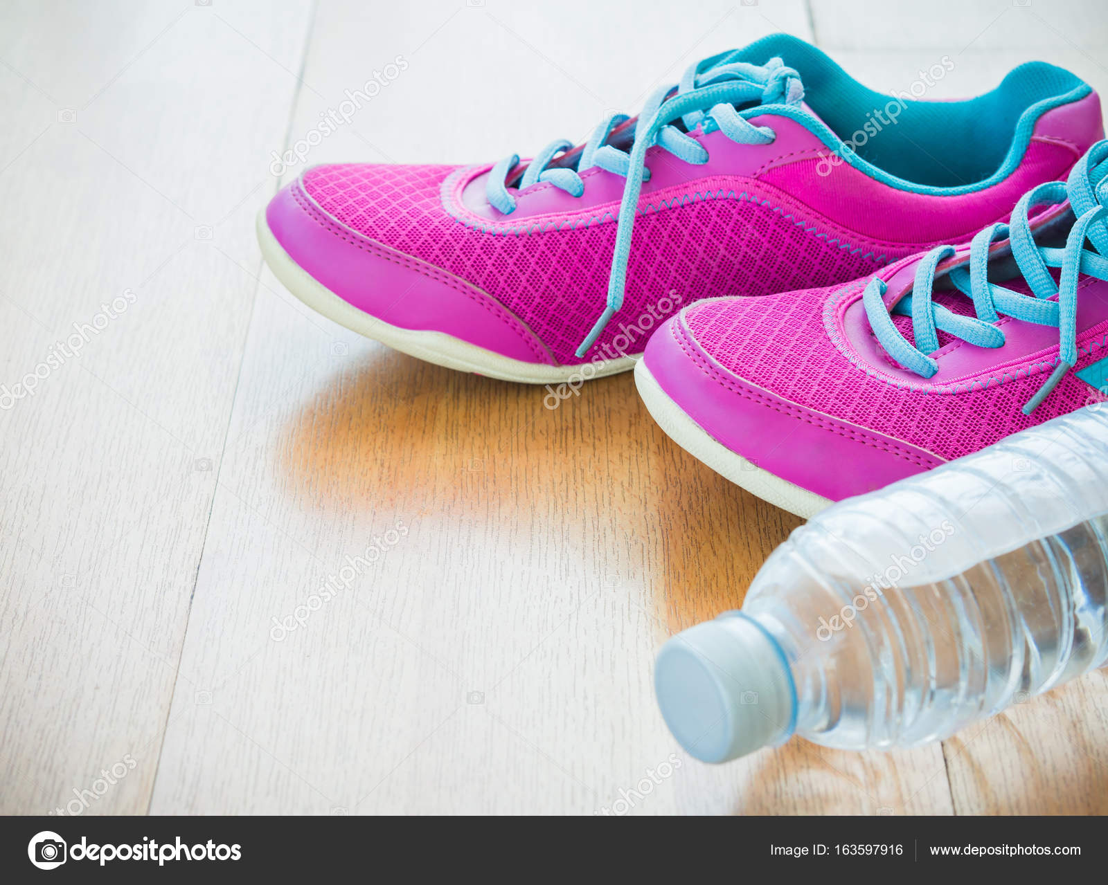 2ae6f51389f53 Pair of pink sport shoes and water bottle with wooden background — Stock  Photo