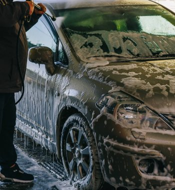 Contactless car wash, foam, pressure, self-service. Man is washing his car