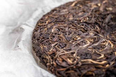 old Shen puerh chinese fermented tea on papyrus paper background macro close-up