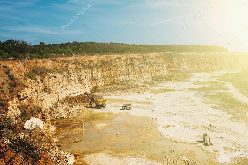 Open cast Quarry with heavy duty machinery equipment in sunlight