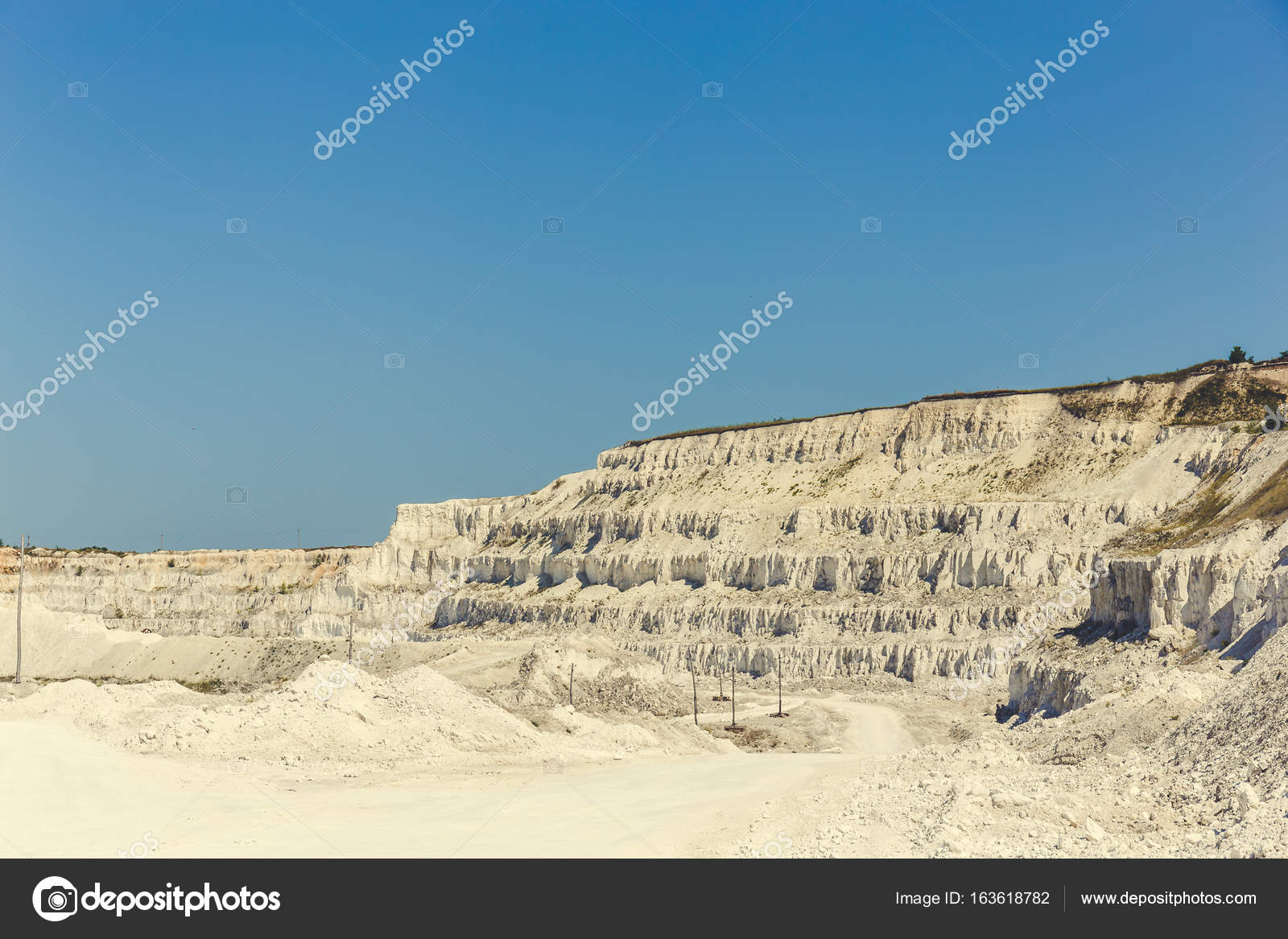 White yellow open cast limestone mining quarry at blue sky