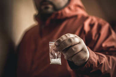 Mans hand holds plastic packet with cocaine powder, selective focus