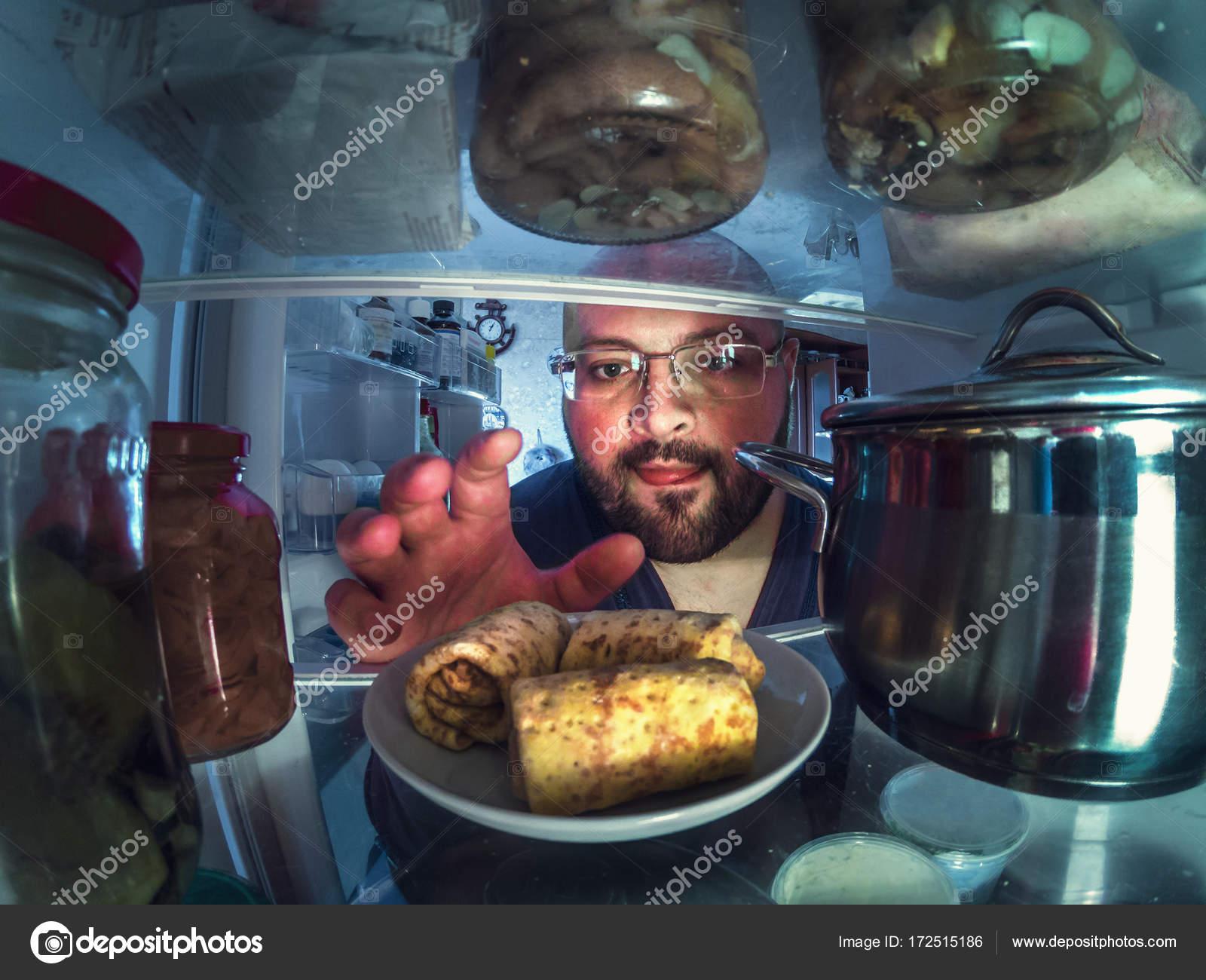 Kühlschrank Platte : Hungriger junge mann nimmt platte mit pfannkuchen aus offenen
