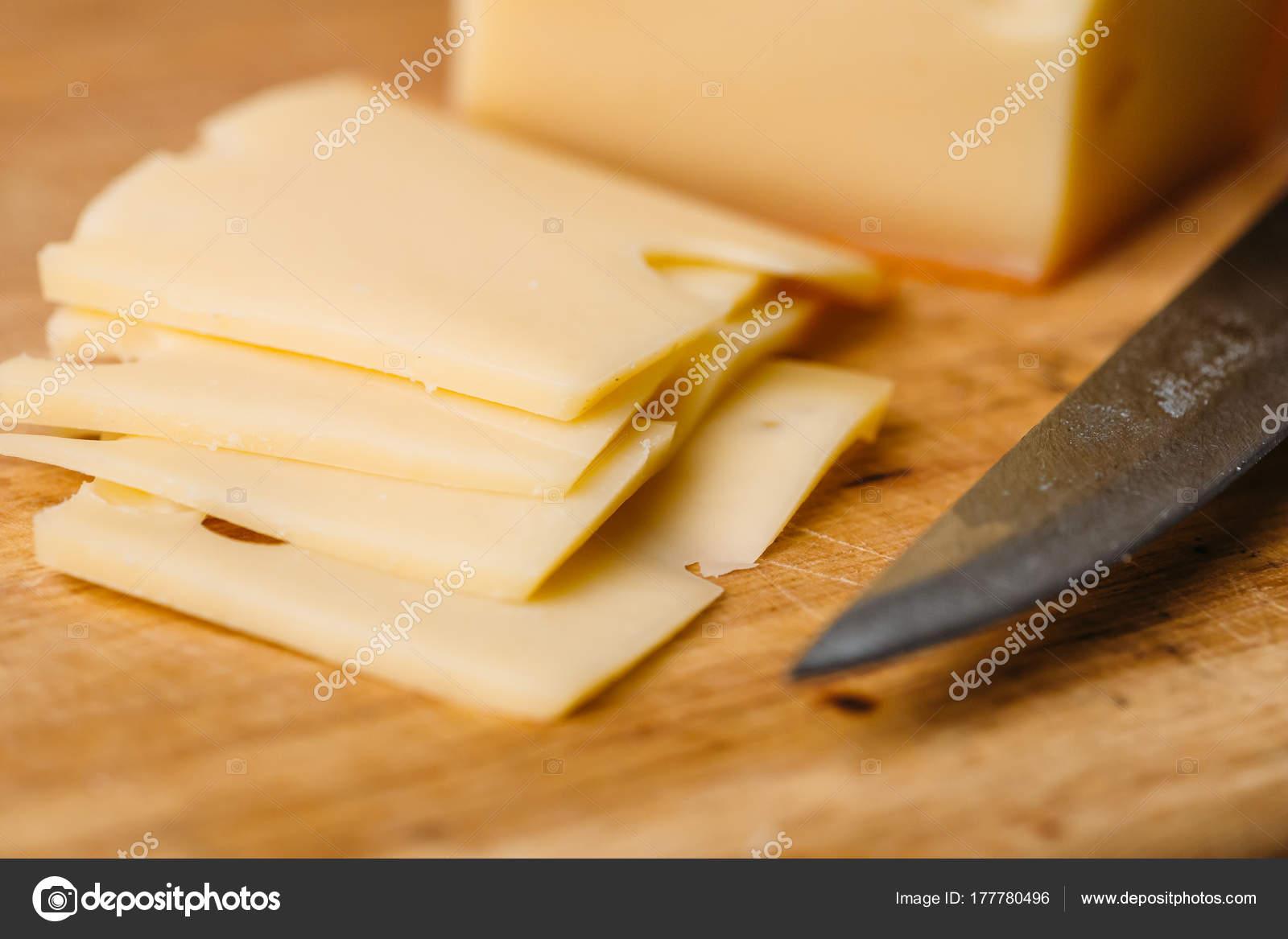 Champi ones con queso provolone trozos de queso en la tabla de cortar madera y cuchillo foto - Cuchillo cortar queso ...