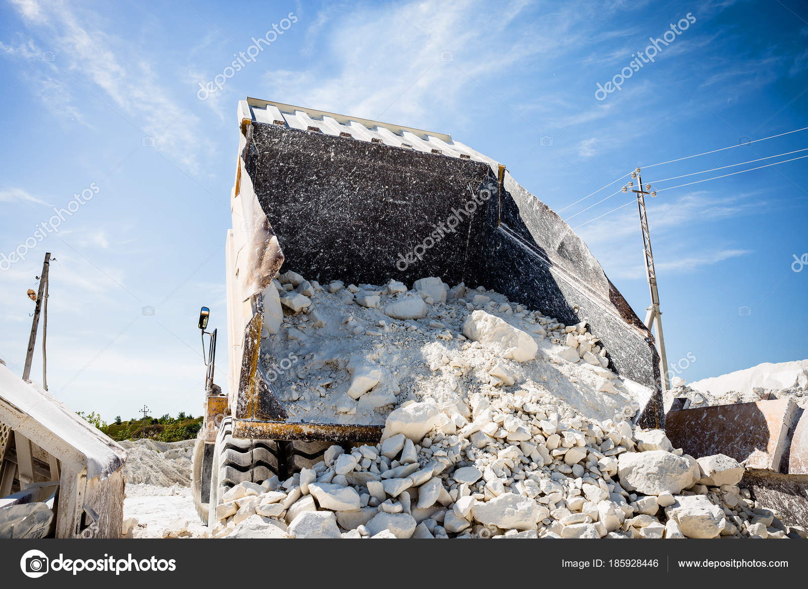 Big quarry truck unloads white limestone gravel to crushed