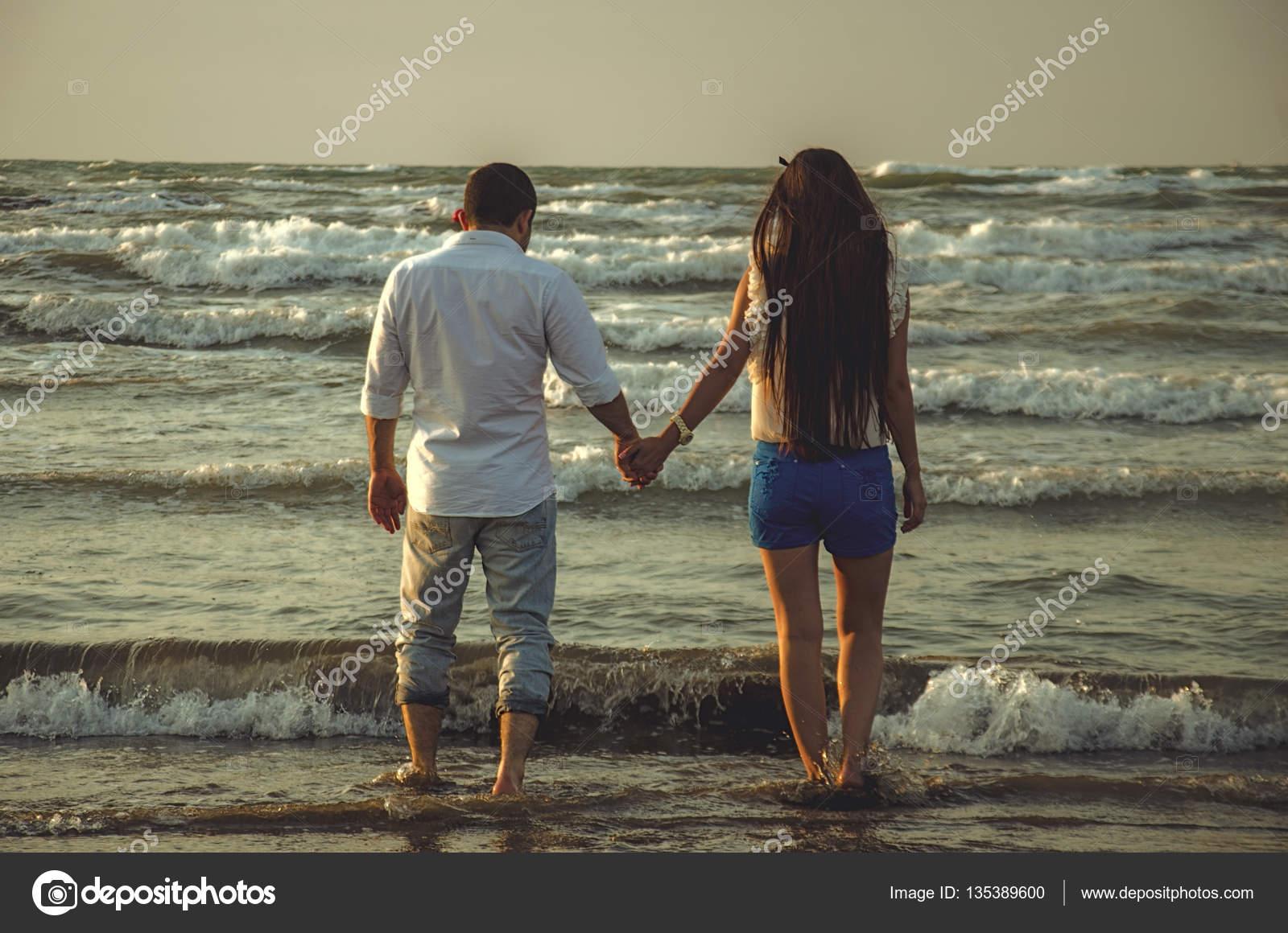 Happy držel ruku pár na pláži s vlnami moře nebo krásný pár na mořské  pobřeží. Láska c408fe4d195