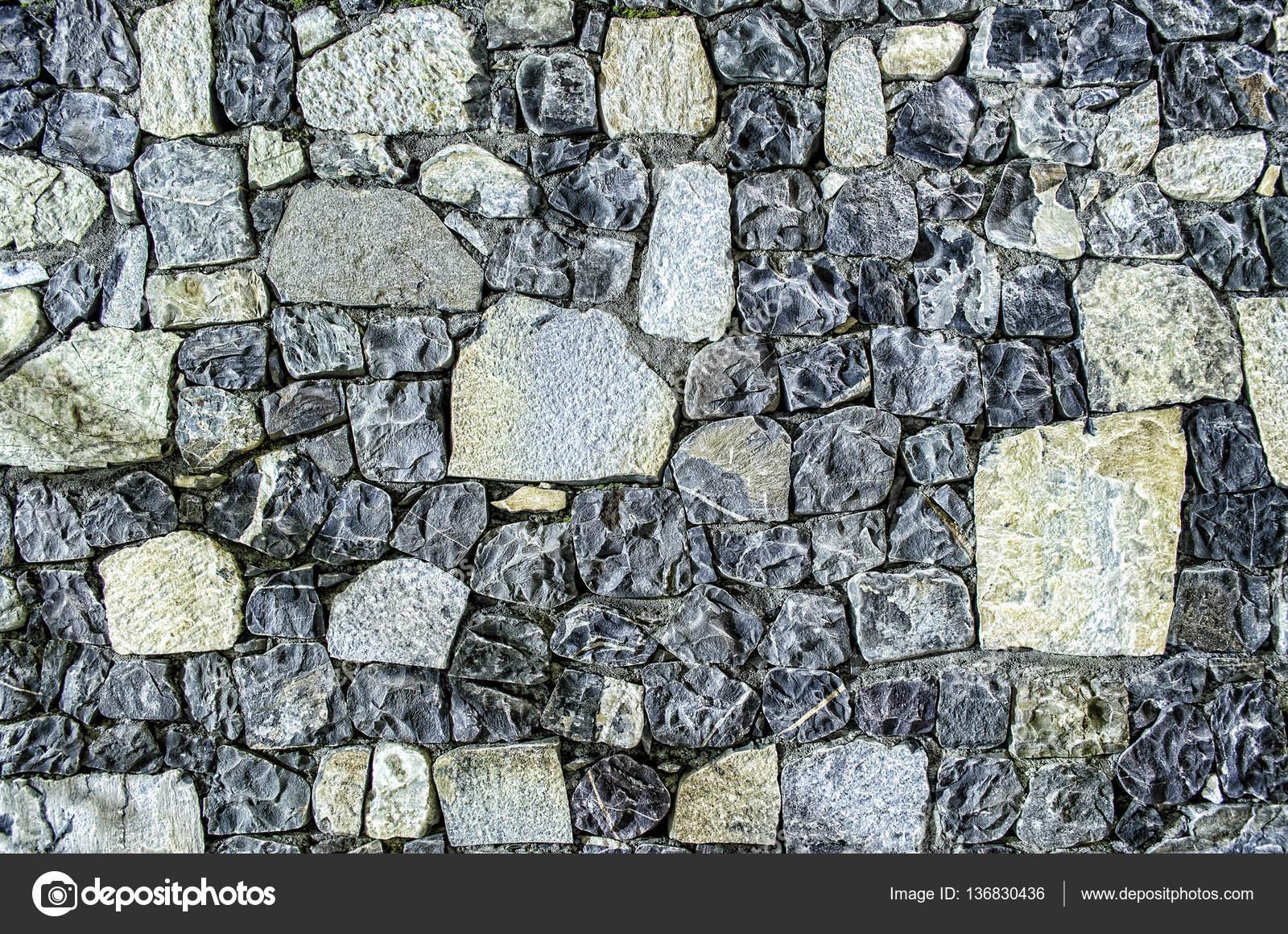 Frammento di vecchio muro di mattoni con fiume pietre texture bianco grigio marrone nero verde ...