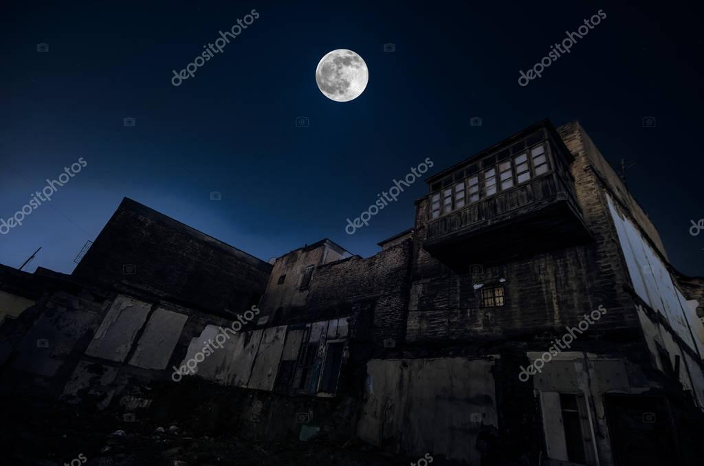 Full moon over the ruins of old grunge building in Baku at night, house with balcony. Sovetsky, Azerbaijan