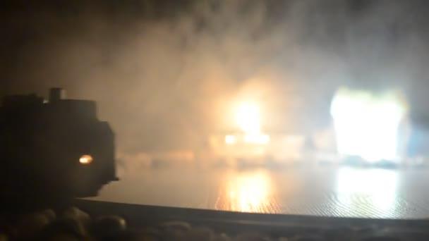 Vlak, pohybující se v mlze. Starodávné parní lokomotiva v noci. Noční vlak na železniční trati. oranžový oheň pozadí. Mystické scéna horor