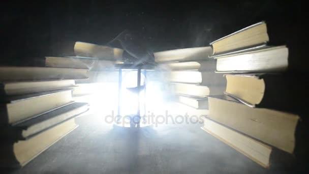 Sok régi könyvet egy verem. Knoledge koncepció. Könyvek a sötét háttéren füst elemekkel. Bewitched könyv közepén. Glasswatch