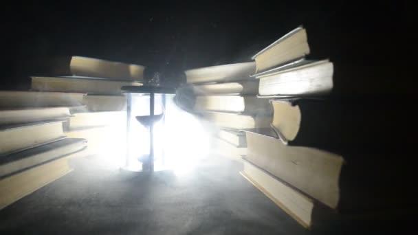 viele alte Bücher in einem Stapel. knoledge Konzept. Bücher auf dunklem Hintergrund mit Raucherelementen. Zauberhaftes Buch in der Mitte. Glasuhr