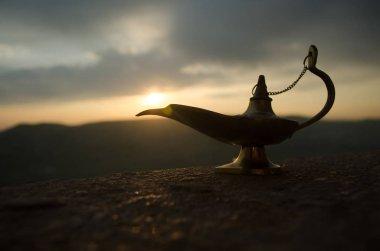 Antique artisanal Aladdin Arabian nights genie style oil lamp with soft light white smoke. Sunset mountain background