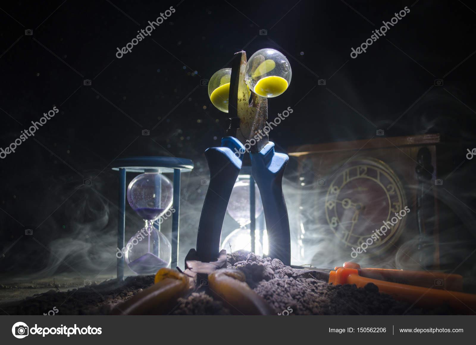 Zeit Konzept. Silhouette Der Sanduhr Uhr Und Rauch Auf Dunklem Hintergrund  Mit Warmen Gelb Orange
