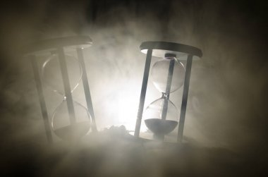 Time concept. Silhouette of Hourglass clock and smoke on dark background with hot yellow orange lighting, or symbols of time with copy space, sandglass or sand clock