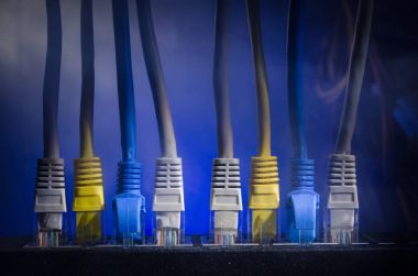 Network switch and ethernet cables, symbol of global communications. Colored network cables on dark background with lights and smoke. Selective focus