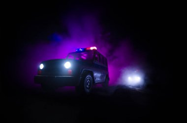 speed lighting of police car in the night on the road. Police cars on road moving with fog. Selective focus. Chase