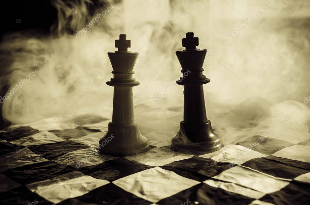 chess board game concept of business ideas and competition and strategy ideas concep. Chess figures on a dark background with smoke and fog and window with sunlight.