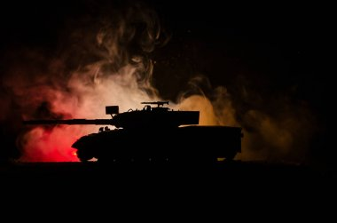 War Concept. Military silhouettes fighting scene on war fog sky background, German tank in action Below Cloudy Skyline At night. Attack scene. Armored vehicles
