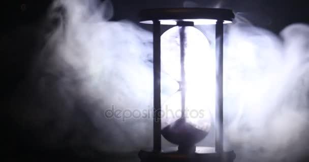 Idő fogalmát. Sziluettjét homokóra óra forog a füst, sötét tónusú háttér, vagy szimbólumok mellett, füst, a végén