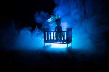Old creepy eerie wooden baby crib in dark toned foggy background. Horror concept. Scary baby and bed silhouette in dark