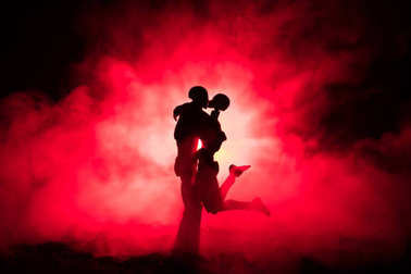 Love Valentine`s Day concept.Sillhouette of sweet young couple in love standing in the field and hugging on dark toned foggy background. Decoration with doll figures on table shot.