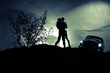 Silhouette of couple kissing under full moon. Guy kiss girl hand on full moon silhouette background. Valentine`s day decor concept