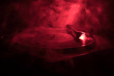 Turntable vinyl record player. Retro audio equipment for disc jockey. Sound technology for DJ to mix & play music. Vinyl record being played against burning fire background
