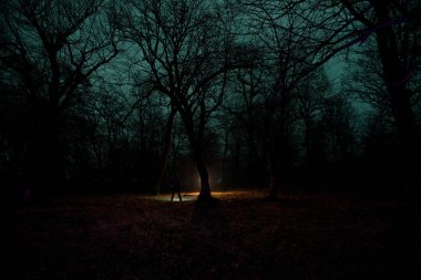strange light in a dark forest at night. Silhouette of person standing in the dark forest with light. Dark night in forest at fog time. Surreal night forest scene. Horror halloween concept.
