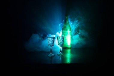 Two glasses of Vodka with bottle on dark foggy club style background with glowing lights (Laser, Stobe) Multi colored. Club drinks theme decoration. Empty space. Selective focus