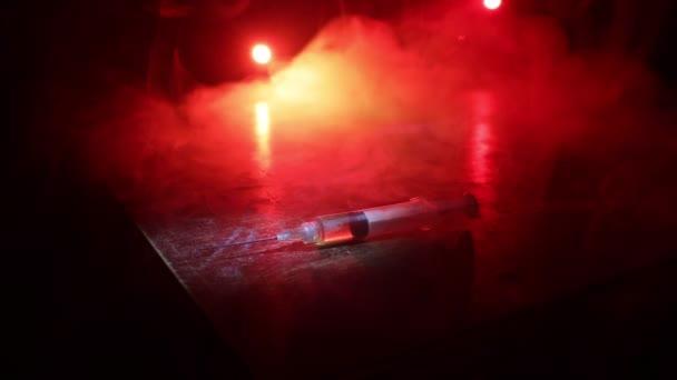 Betäubungsmittelproblem. Silhouette eines Mannes, der in einer nebligen Nacht mitten auf der Straße steht, mit einer riesigen Drogenspritze und Rauschgift-Attributen. Kreative Dekoration