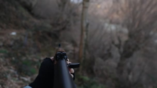 cropped footage of bandit aiming rifle on nature