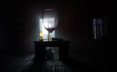 A realistic dollhouse living room with furniture and window at night. Abstract empty vineglass inside dollhouse. Concept of stay home during global virus pandemic. Selective focus.